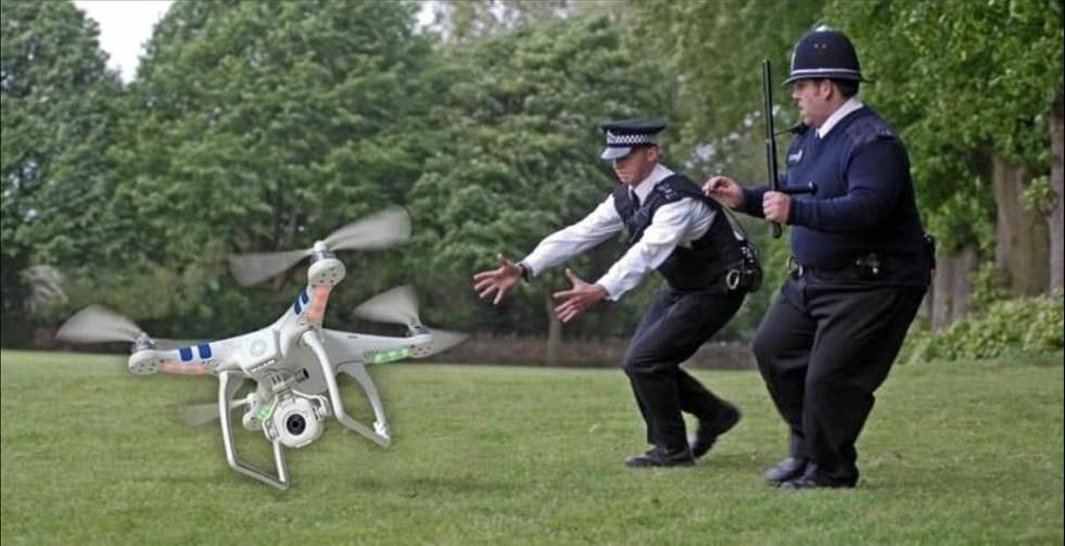 Two Police Men trying to catch their drone.