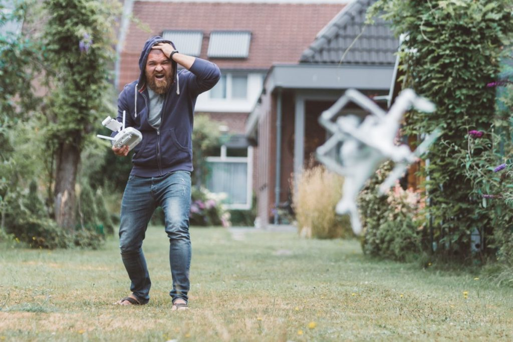Shocked guy with beard looking his drone falling down
