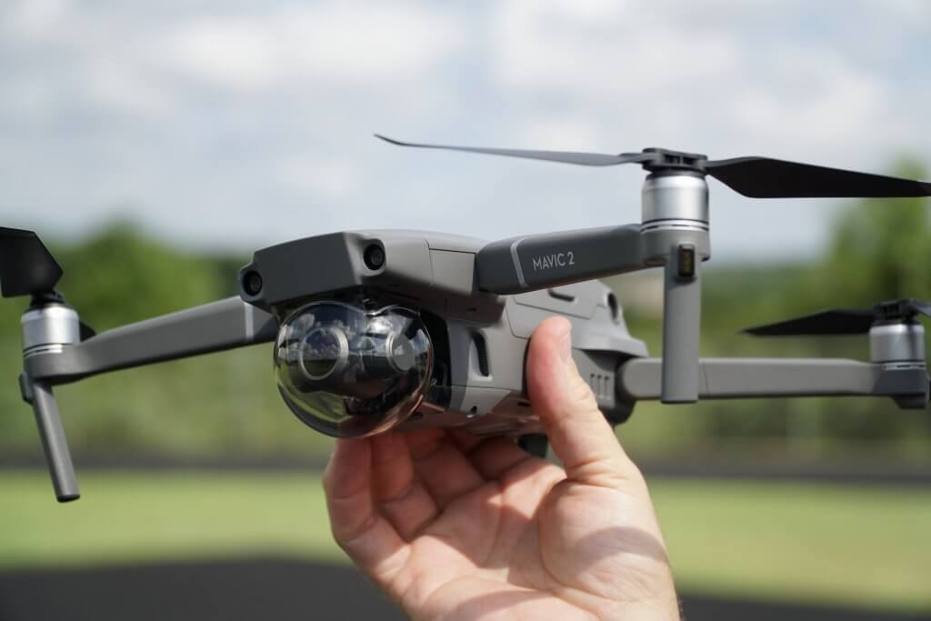 A person holding a DJI Mavic 2 drone in his hands