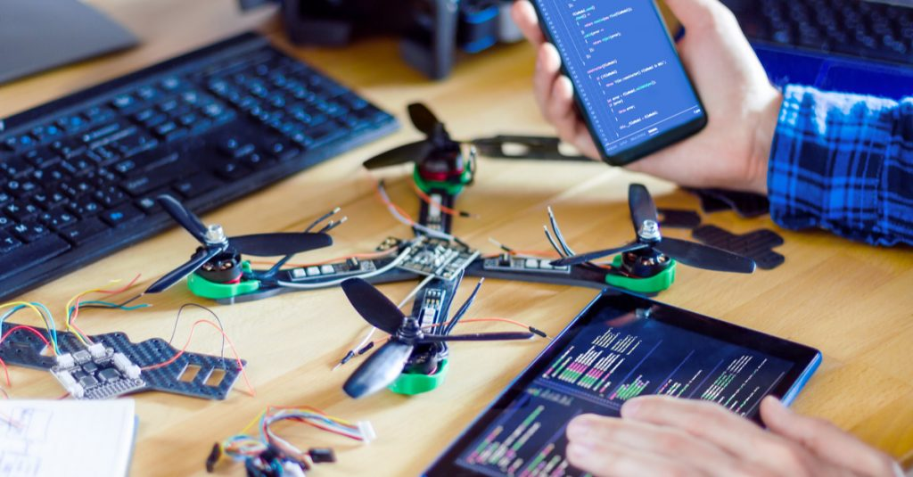 A programmer programing his drone with his phone