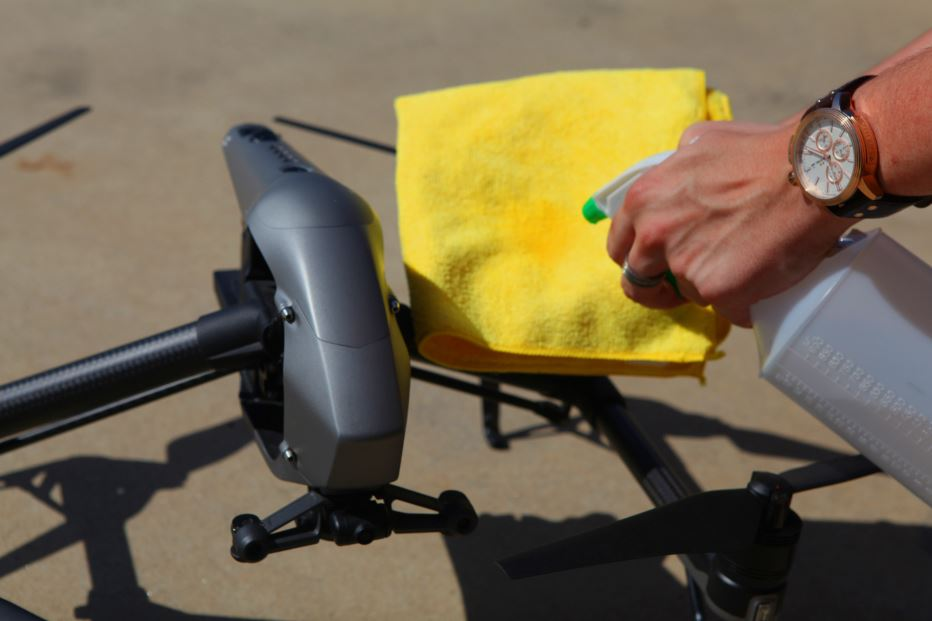 A person cleaning a drone with a cloth and spray.