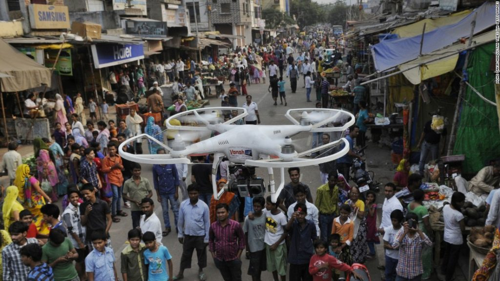 A drone flying above a lot of people in a local market